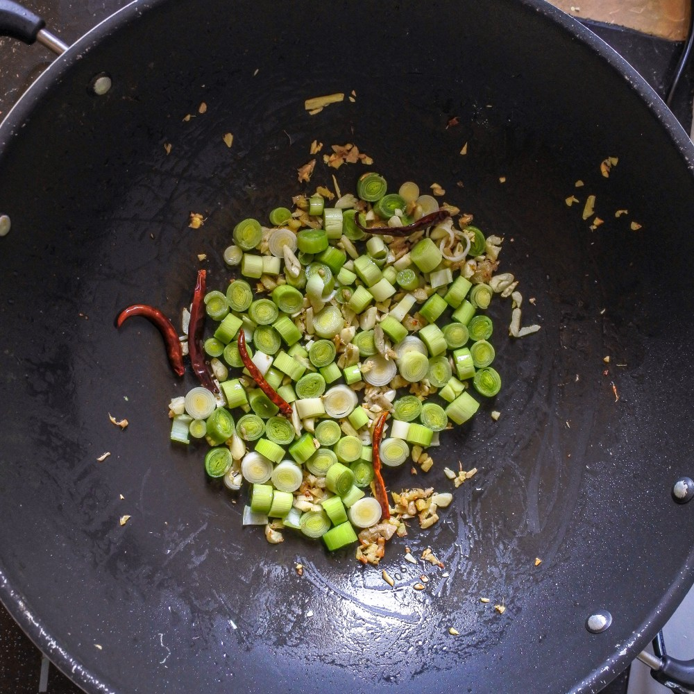 leeks/scallions frying with garlic, ginger and peppers