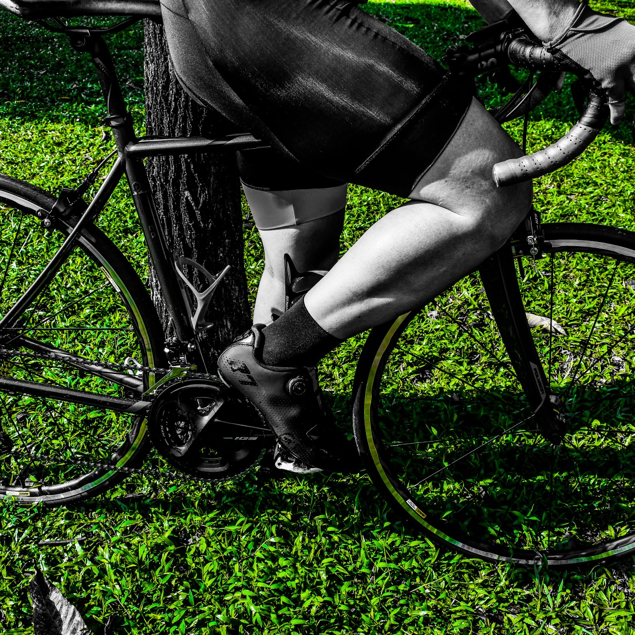 A shadowed picture of a man on his bike in grey and green