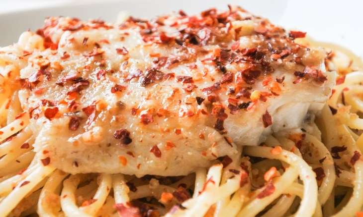 Anchovy pasta topped with white fish and red pepper flakes