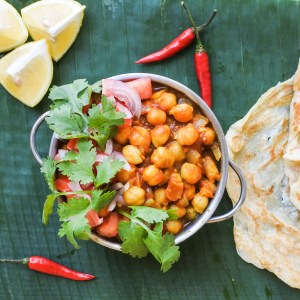 A bowl of curried chickpeas garnished with chopped tomatoes, onion and cilantro served alongside lemon wedges, red chiles and roti