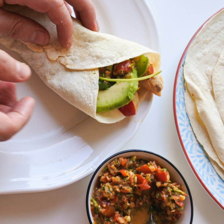 A hand folding a tortilla around fajita mix, avocado and salsa