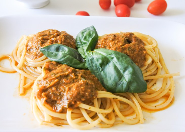 A plate of spaghetti covered in red sauce and garnished with Basil