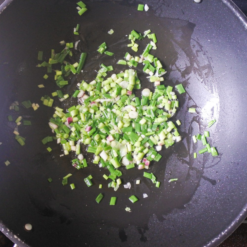 Chopped scallions cooking in butter in a large pan