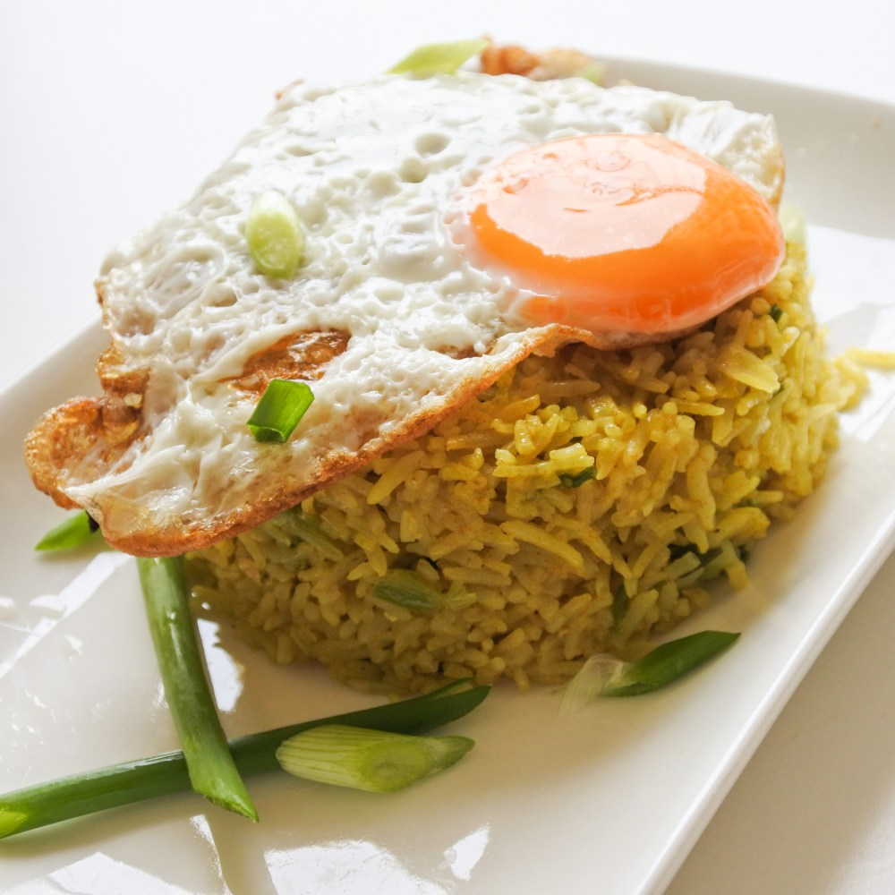 A sunny side up egg atop a mound of curried rice garnished with chopped scallions