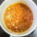 Beans, chicken broth, onion, garlic and spice cooking in a pot