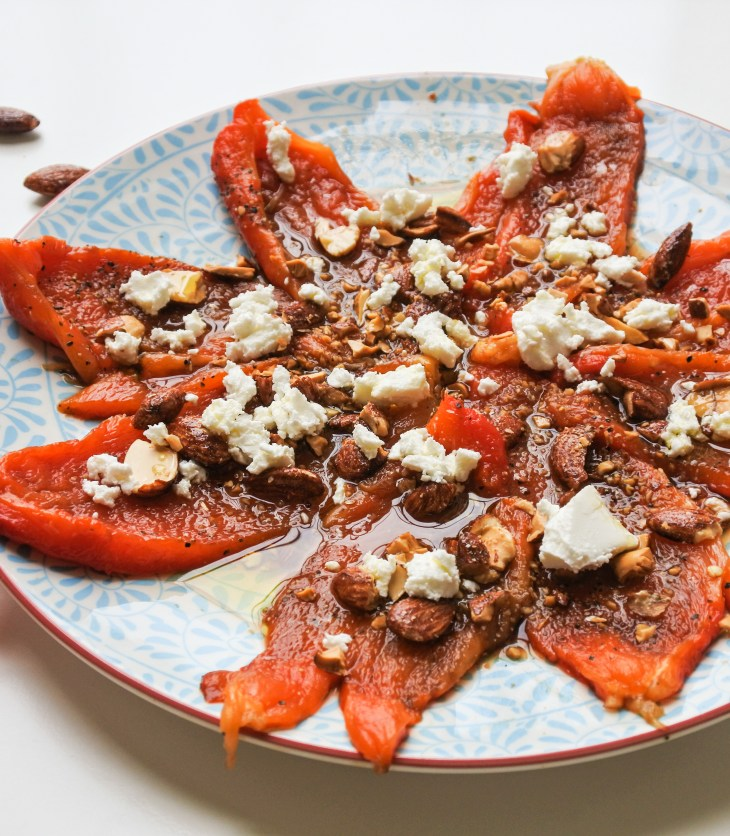 A flower of roasted red peppers topped with white goat cheese and roasted almonds served alongside slices of raw red pepper