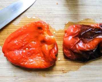 Roasted red peppers on a wooden cutting board with a knife