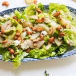 Lettuce leaves topped with roasted pear slices, roasted cashews and blue cheese crumbles