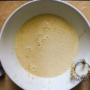 Wet ingredients for banana pancakes in a large white bowl