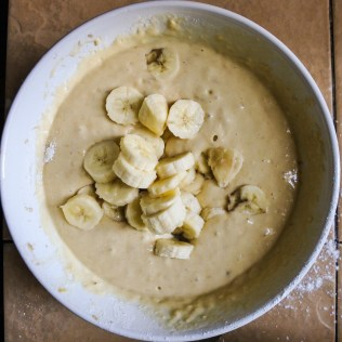 Sliced bananas added to lumpy pancake batter in a large white bowl
