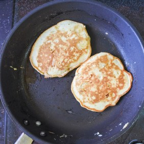 Two golden browned pancakes cooking in a pan