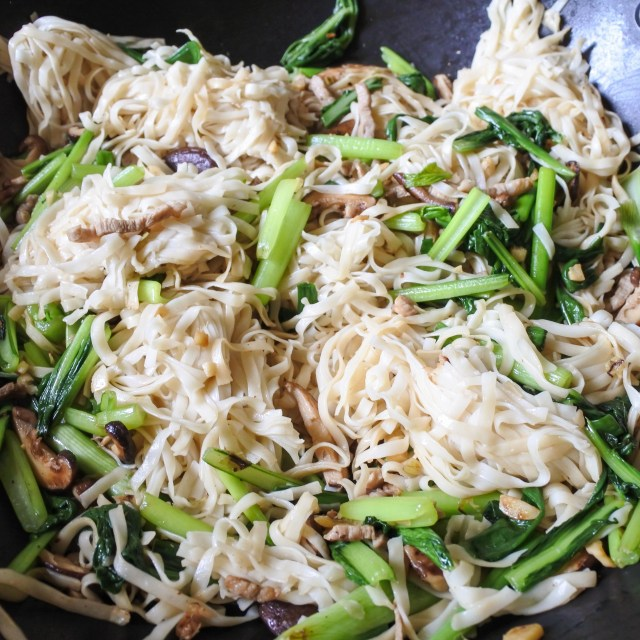 Cooked Chinese egg noodles cooking in a wok with Choy sum, mushrooms and pork mixture