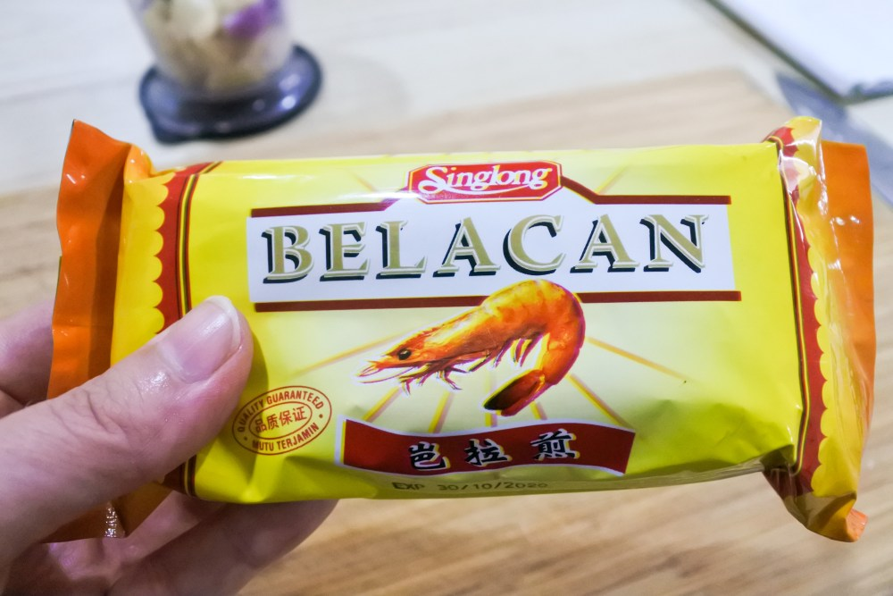 An orange rectangular package of Belacan shrimp paste