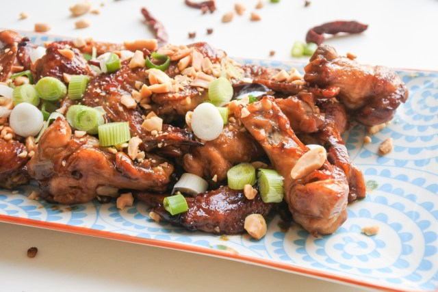 A party plate of Kung Pao Chicken wings garnished with chopped green scallions and peanuts