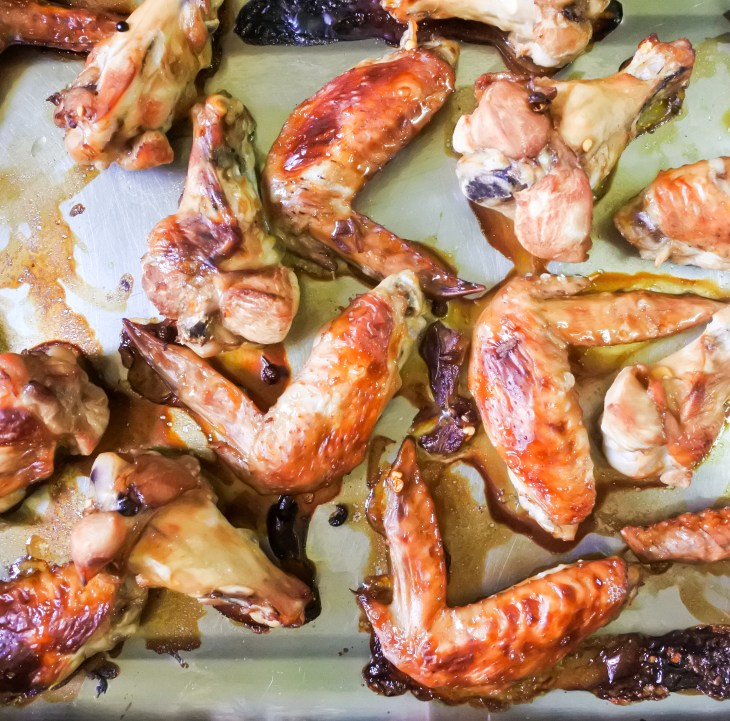 An oven tray of golden brown roasted chicken wings.