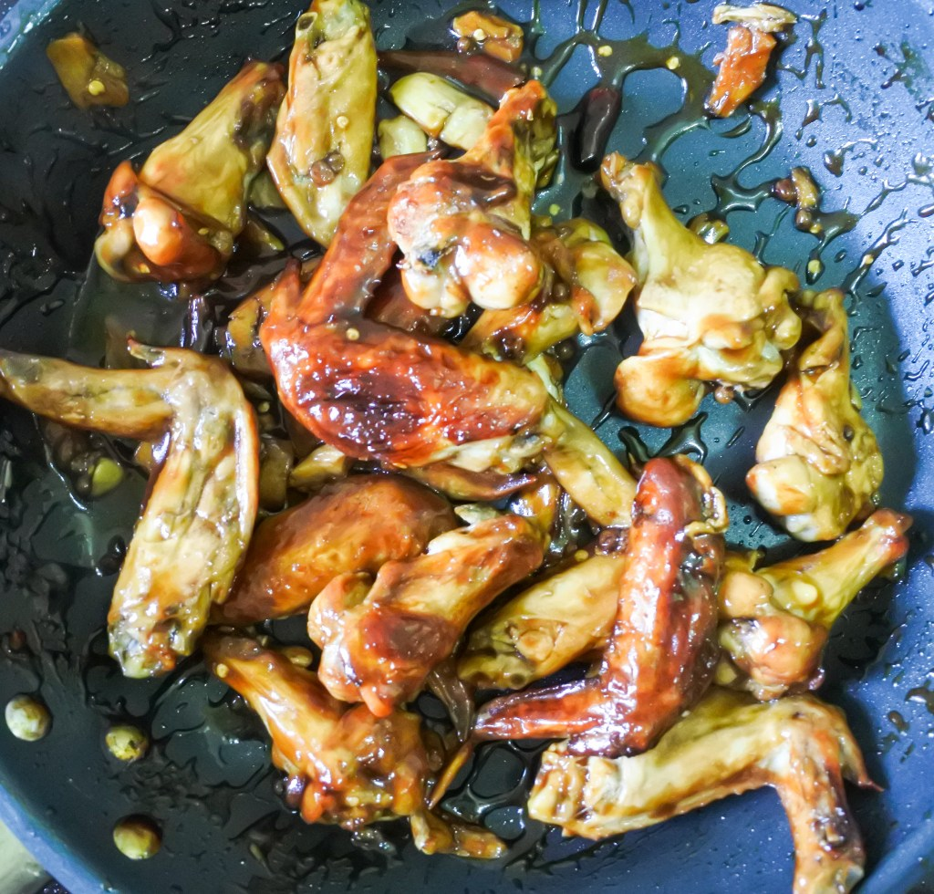 Roasted chicken wings being tossed in a thickened Kung Pao Sauce