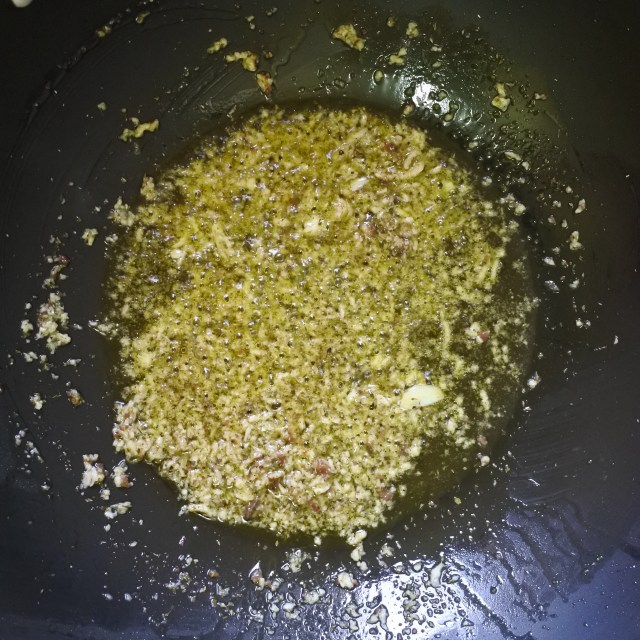 A sauce of minced garlic, anchovies, oregano and olive oil frying in a pan