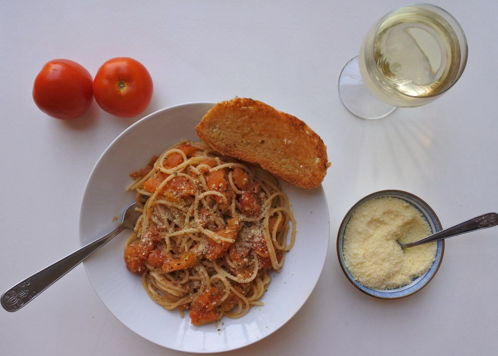 Spaghetti tossed with roasted tomatoes served with garlic bread, white wine and Parmesan cheese