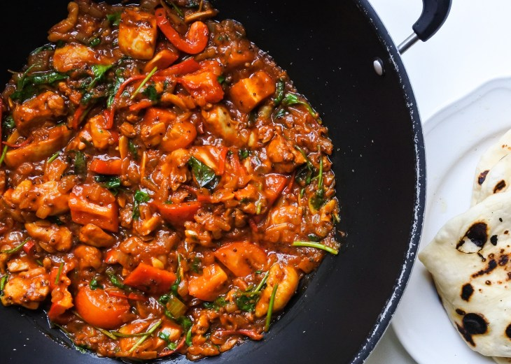 Chicken Balti in a wok with a plate of naan