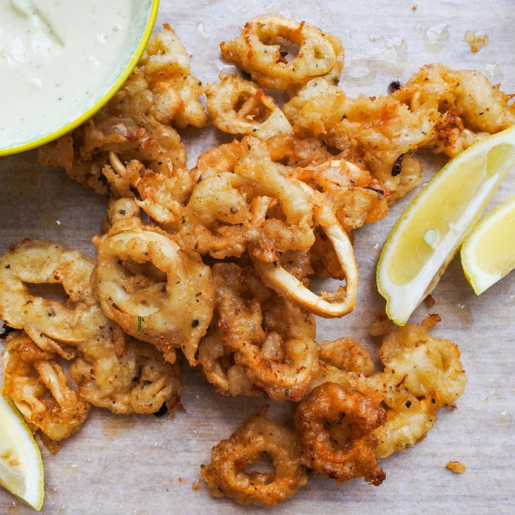 A mound of crispy, golden fried calamari rings with lemon wedges and a creamy aioli