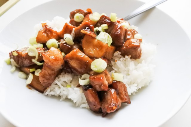Pork shoulder and king oyster mushroom stir-fry atop steamed jasmine rice garnished with chopped scallions