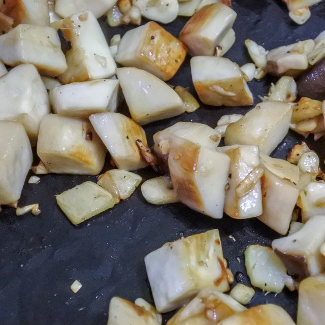 Chopped king oyster mushrooms frying until golden brown in a wok