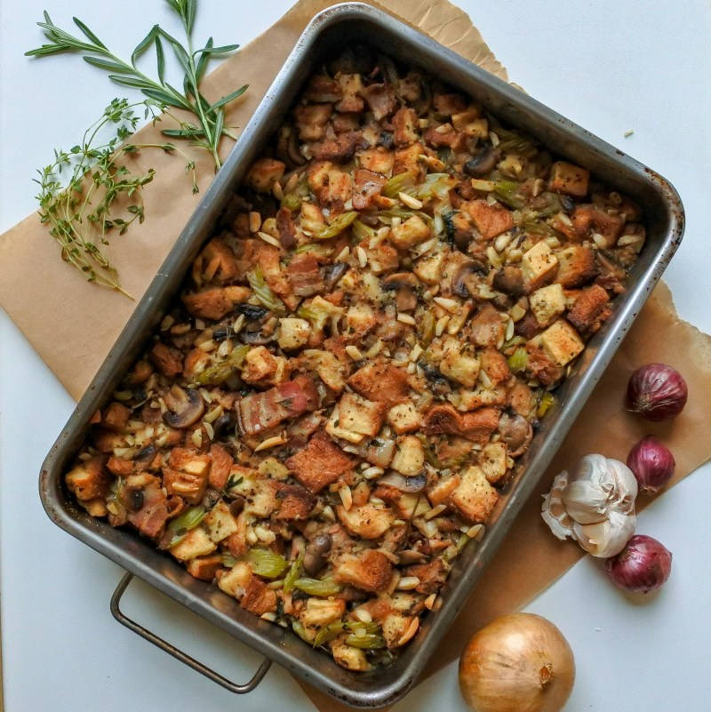 Bacon and almond stuffing in a pan with herbs, garlic and onions