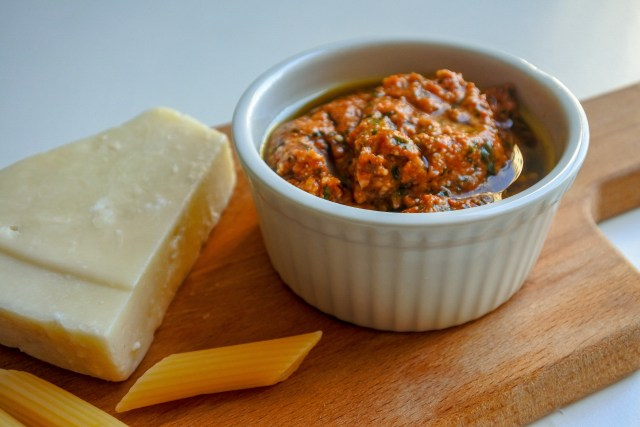 red pepper pesto in ramekin on a board with cheese and penne