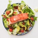 a fillet of salmon over lettuce with avocado, roasted cherry tomatoes, shallots and bacon