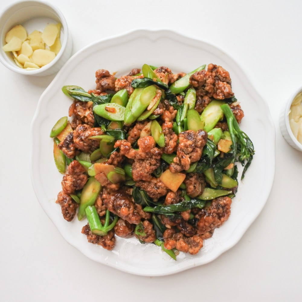 beef and broccoli on a plate next to a bowl of sliced ginger