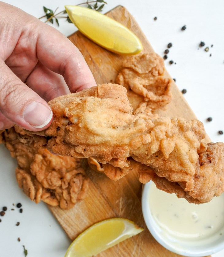 Crispy chicken tender next to lemon wedges and ranch sauce