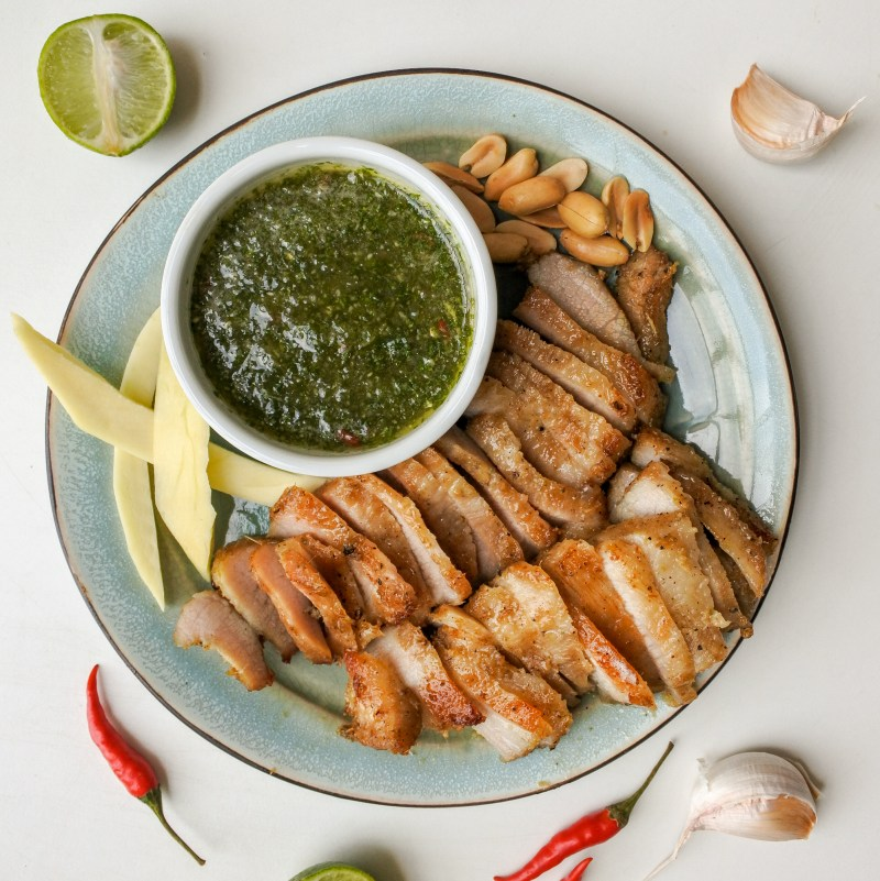 Sliced grilled pork jowl on a plate with mango slices, peanuts, limes, garlic and red chiles