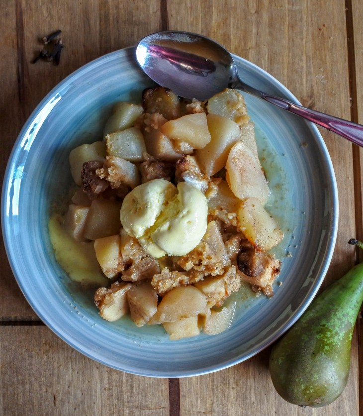 Spiced apple and pear crumble on a plate with vanilla ice cream on top