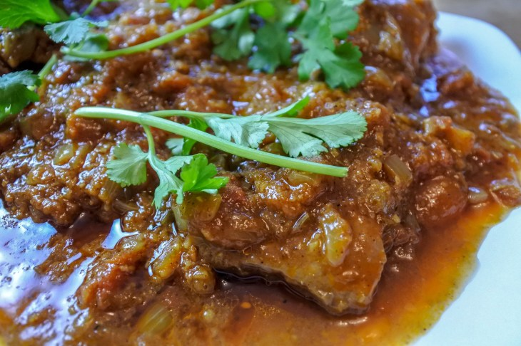 lamb flank curry on a plate garnished with cilantro