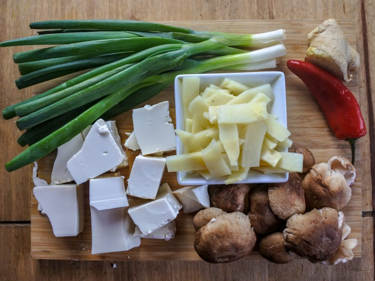 scallions, tofu, bamboo shoots, mushrooms, ginger and red chili on a wooden cutting board