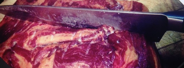 Large butcher knife cutting through bloody steak.