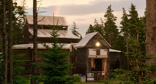 Large wood theatre building in the woods with bright colourful rainbow arching overhead.