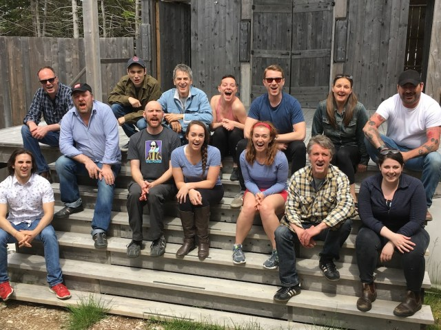 Goofy shot of large cast sitting infront of wood cabin.