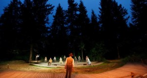 A forest clearing at night. A large cast of actors in tableaux across the clearing, dressed in early 1900s clothing.