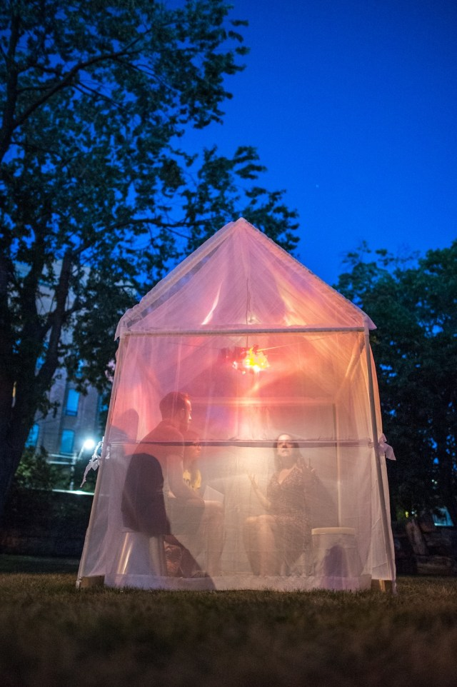 A tent made of clear plastic with pinks and yellow lights inside.