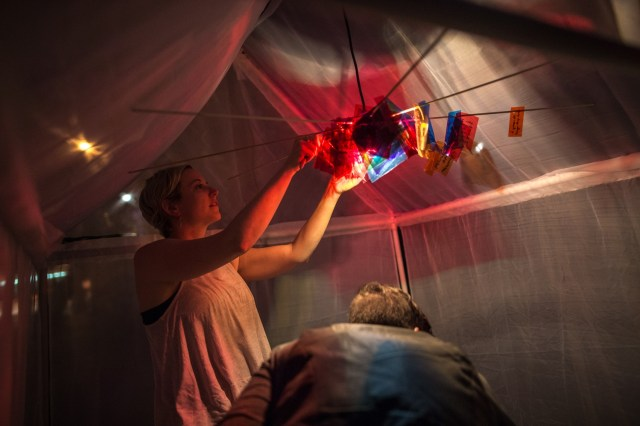A woman hangs colourful pieces of paper along the inside of a tent.