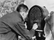 Black and white photo of man tinkering with old time wooden radio.