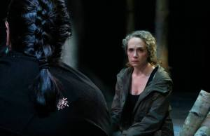 Peering over the shoulder of a man with braided hair. He faces a dejected looking woman with curly blonde hair.