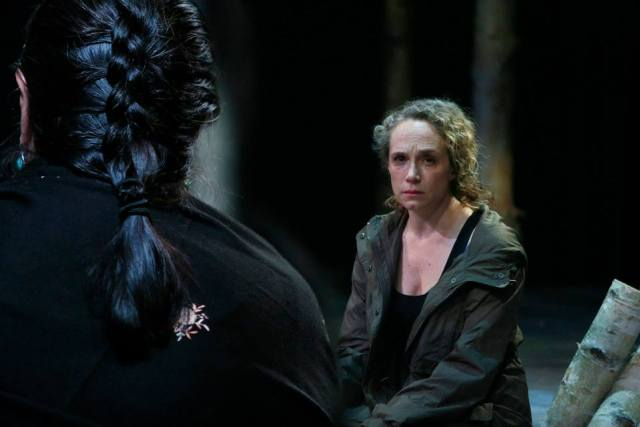 Peering over the shoulder of a woman with braided hair. He faces a dejected looking woman with curly blonde hair.