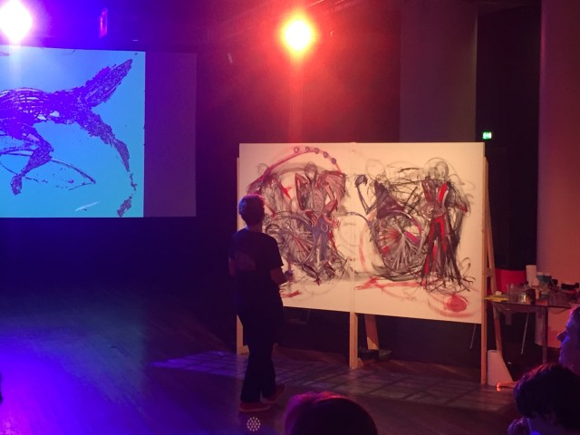 Colourful light stage with an artist painting a large canvas. Their painting is references images of wheelchairs with expressive lines.