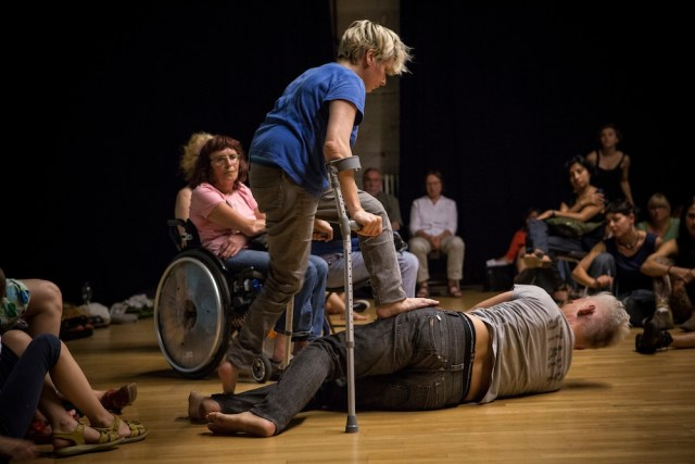 Audience seated casually around performers in centre of floor. One performer using crutches steps onto the hip of another performer laying on the floor.