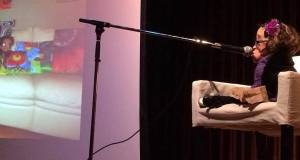 Elaine sits on a comfy white chair on stage, speaking into a microphone. Behind her is a projection screen with an image of a couch on it.