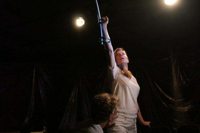 Debbie stands on stage in all white, with one arm extended above her pointing her crutch up to ceiling.