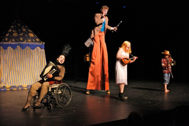 4 performers on stage in a circus style show. One on stilts, Debbie using a wheelchair, all playing instruments.
