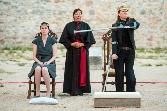 3 actors perform in a sandy outdoor space, in front of a stone wall. Debbie, in a crown, angrily points towards another crowned actor who is seated. An actor dressed like a bishops laughs in the background.